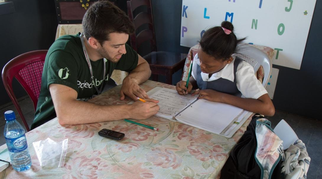 Teaching volunteer in Argentina helps a student with her reading skills